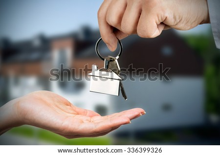 Man gives a woman the keys to a new home. Chrome pedant with house shape - stock photo