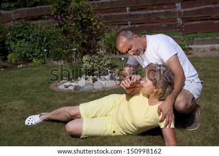 Man gives senior woman with heat exhaustion something to drink - stock photo