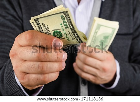 man gives some of the money, closeup - stock photo