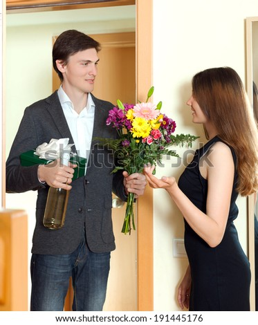 Man giving a gift box to his young wife at home door - stock photo