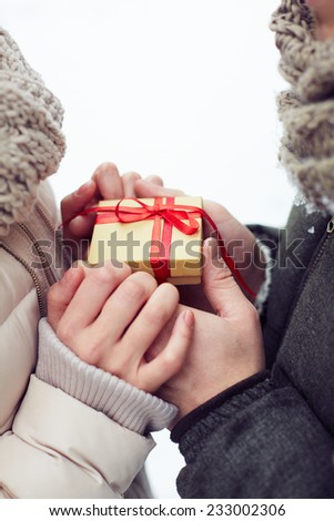 Man giving a little gift box to his girlfriend - stock photo