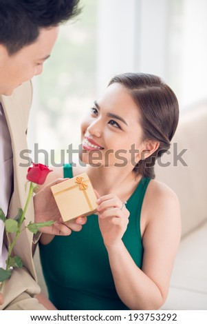 Man giving a present and rose to his girlfriend - stock photo