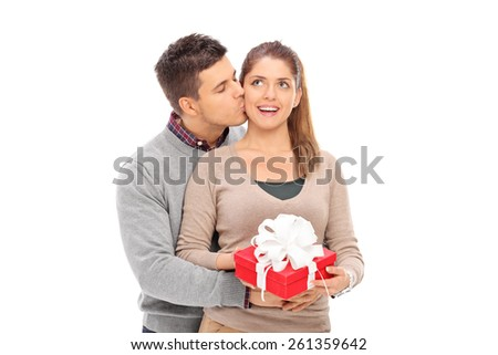 Man giving a present to his girlfriend and kissing her isolated on white background - stock photo