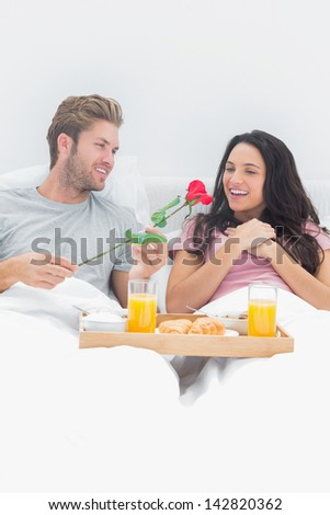 Man giving a rose to his wife during breakfast in bed - stock photo