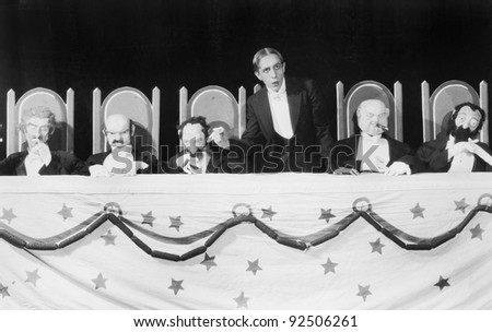 Man giving a speech with five character puppets sitting at the table - stock photo