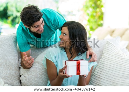 Man giving a surprise gift to woman at home - stock photo