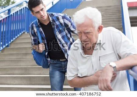 Man giving aid to senior walking downstairs - stock photo