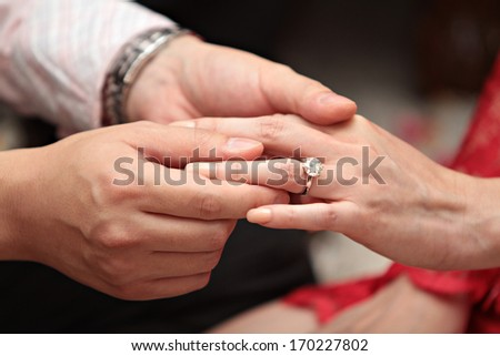 Man giving an engagement ring to his girlfriend - stock photo