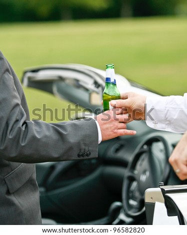 man giving another man a bottle of beer/lager while standing next to a convertible motor vehicle, dangers of drinking and driving - stock photo