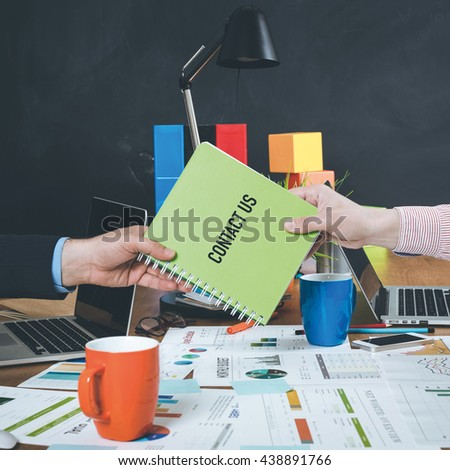 Man giving book which written Contact Us - stock photo