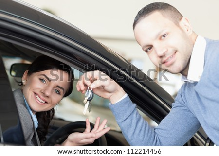 Man giving car keys to a woman thru a window - stock photo