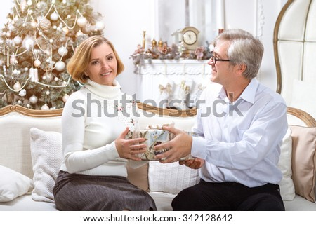 Man Giving Christmas Present To His Wife In White Interior. Christmas Theme - stock photo