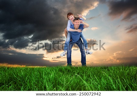 Man giving girl a piggy back against blue and orange sky with clouds - stock photo