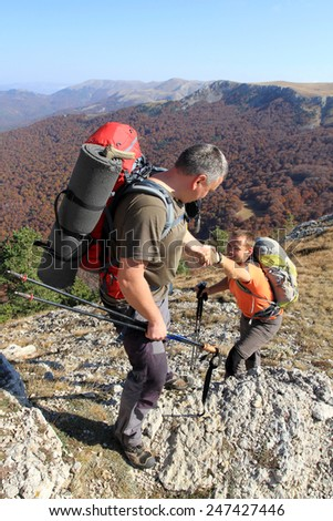 Man giving helping hand to friend to climb mountain rock cliff - stock photo