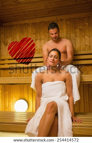 Man giving his girlfriend a neck massage in sauna against red heart - stock photo