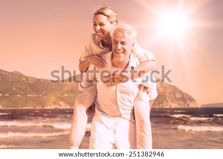 Man giving his laughing wife a piggy back at the beach on a sunny day - stock photo