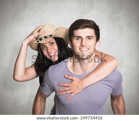 Man giving his pretty girlfriend a piggy back against weathered surface - stock photo