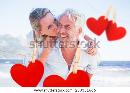 Man giving his smiling wife a piggy back at the beach against hearts hanging on a line - stock photo