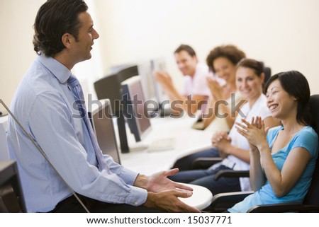 Man giving lecture in applauding computer class - stock photo