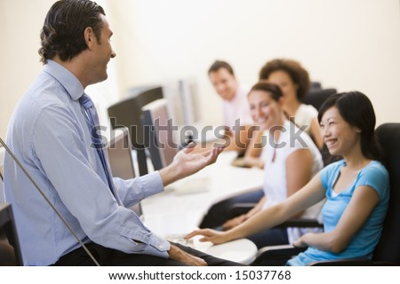 Man giving lecture in computer class - stock photo