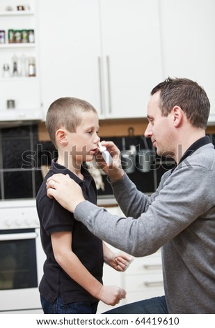 Man giving nose drops to young boy - stock photo