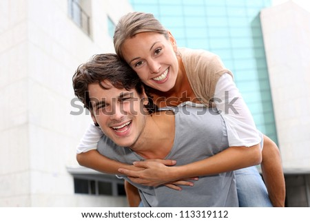 Man giving piggyback ride to girlfriend - stock photo