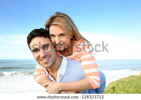 Man giving piggyback ride to girlfriend by the sea - stock photo