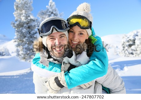 Man giving piggyback ride to girlfriend in snowy mountain - stock photo
