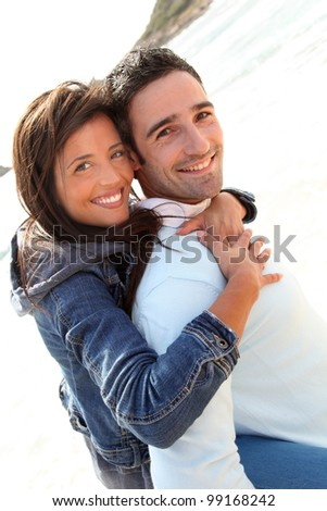 Man giving piggyback ride to girlfriend on the beach