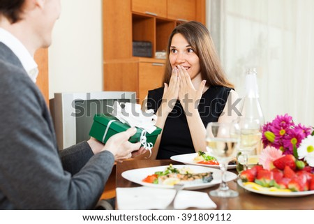 Man giving present woman during romantic dinner in home