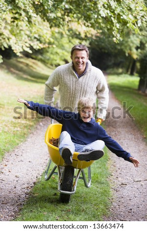 Man giving son ride in wheelbarrow on autumn path - stock photo