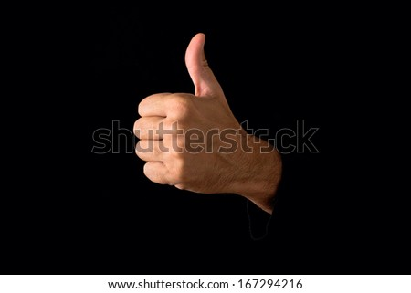 Man giving thumb up on dark black background.