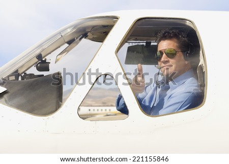 Man giving thumbs up in cockpit of airplane - stock photo