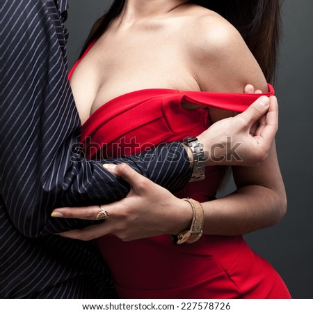 Man grabbing her dress. Outdoors shot - stock photo