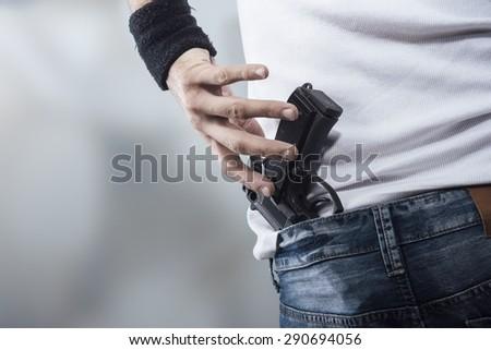 Man grabbing quickly a pistol, hands close up - stock photo
