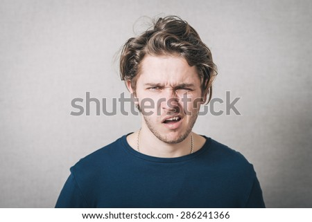Man grimaces. Gray background - stock photo