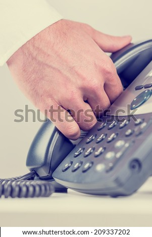 Man gripping a telephone receiver in his hand as he prepares to answer an incoming call on a terrestrial landline conceptual of business communication with vintage filter effect.