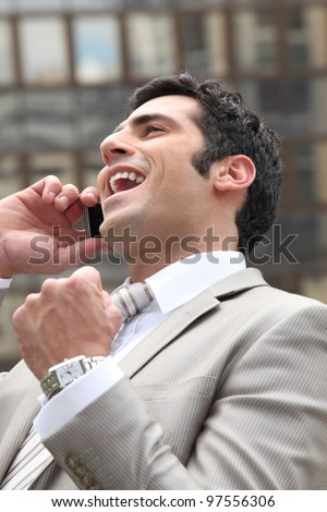 Man guffawing on phone - stock photo