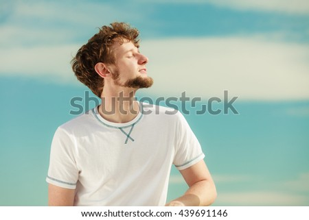 Man guy with closed eyes relaxing enjoying summer sunny day outdoor breating deep fresh air. Vacation holiday.