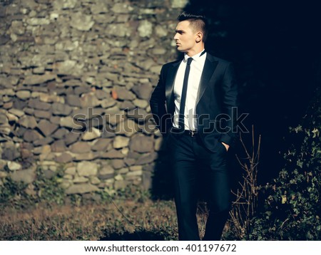 Man half face young handsome elegant model in suit with skinny necktie poses with hands in trouser pockets one leg backward outdoor on masonry background - stock photo