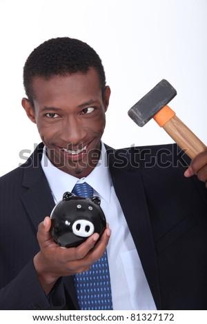 Man hammering open a piggy bank - stock photo