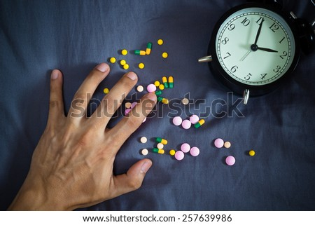 man hand and drugs , tablets suffering insomnia, hangover, headache, overdose on bed at night - stock photo