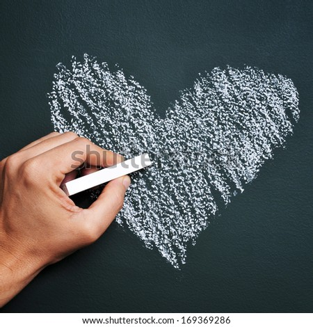 man hand drawing a heart with chalk in a chalkboard - stock photo