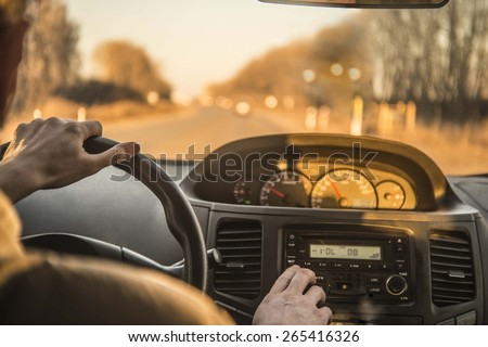 Man hand driving a car at sunset evening sky light Autumn Road between trees forest Male sit inside control volume audio system Finger lie on wheel Empty copy space for inscription  - stock photo