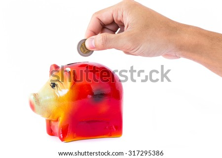 Man hand fill coin into Pig piggy bank saving. The concept of financial assets, reliability deposits, insurance savings. - stock photo