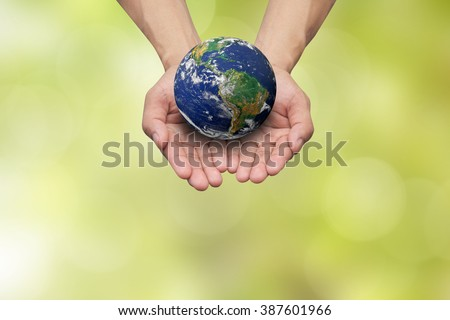 man hand gesture palm up holding world on blurred soft light green foliage background:safe earth energy ecology efficiency:healthcare of planet resource:Elements of this image furnished by NASA. - stock photo