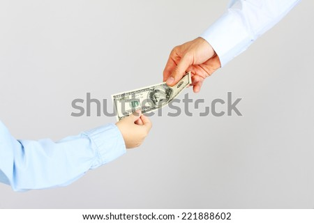 Man hand gives money american hundred dollar bills to boy hand.  Business man give money to business boy. Father and son. - stock photo
