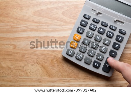 Man hand hold and press Calculator on Wood Background - stock photo