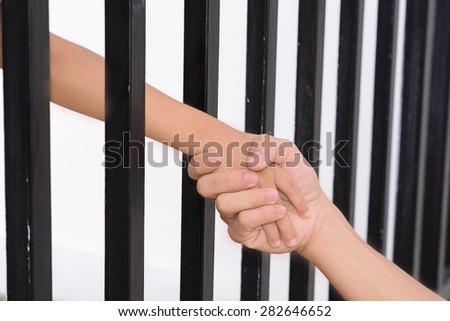 Man hand hold kid hand from the jail