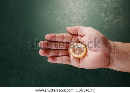 man hand holding a condom - stock photo